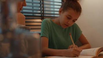 kvinna som hjälper flickan gör läxor vid bordet video