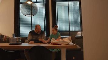 hombre ayudando a niña haciendo los deberes en la mesa video