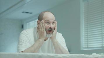 Hombre lavando y secando la cara en el baño. video