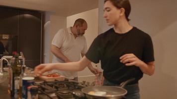 Mann, der Hände wäscht und Frau, die Eier in der Küche backt video
