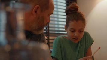 Mann hilft Mädchen, Hausaufgaben am Tisch zu machen video