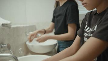 kvinna och flicka tvättar händerna i badrummet video