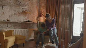 Frau, die Jungen hilft, Hausaufgaben im Sessel zu machen video
