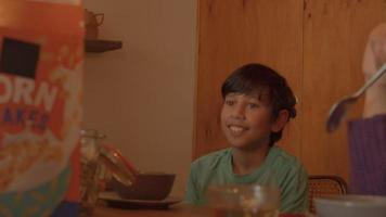 Boy talking with woman at breakfast table video
