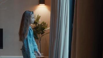 niña caminando a la ventana y mirando por la ventana video