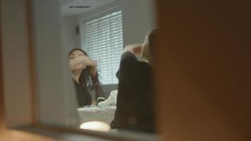 Woman using hairdryer in bathroom looking in mirror video