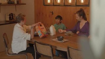 Two women and boy talking at breakfast table video