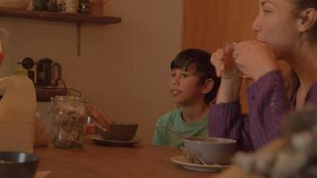 Woman and boy eating cornflakes for breakfast video
