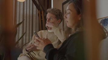 två kvinnor som tittar på tv och smartphone på soffan video