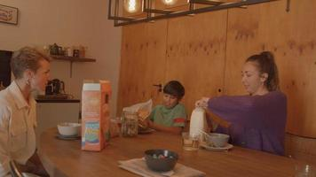Two women and boy having breakfast at table video