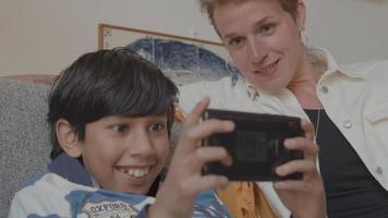 Frau beobachtet Jungen mit Spielekonsole auf der Couch video