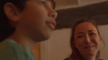 niño y mujer riendo y comiendo en la mesa video