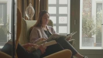 dos mujeres leyendo y hablando en la sala de estar video