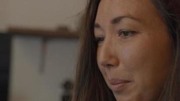 La mujer habla y la pantalla del portátil se refleja en los ojos. video