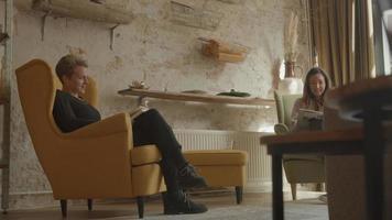 två kvinnor som läser och pratar i vardagsrummet video