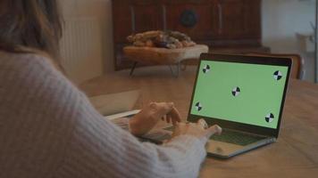 Mujer escribiendo en un portátil con pantalla verde video