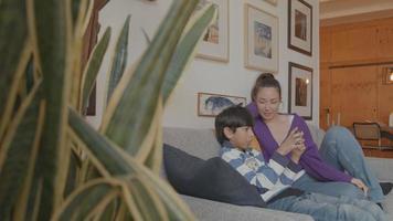 niño jugando con consola de juegos y mujer mirando en el sofá video