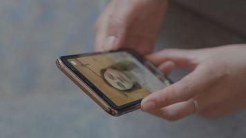manos de mujer sosteniendo teléfono inteligente con videollamada video