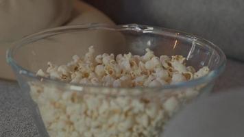 Manos de dos mujeres sacando palomitas de maíz del tazón video