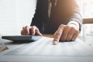 Hombre de negocios usando la calculadora con calcular el gráfico de datos del mercado de valores y el papel de impuestos y presupuestos en la oficina foto