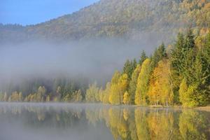 Paisaje de otoño en las montañas con árboles reflejándose en el agua en el lago de Santa Ana, Rumania foto