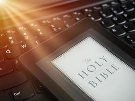 Close up of ebook reader with The Holy Bible on a laptop keyboard with sun rays light concept photo