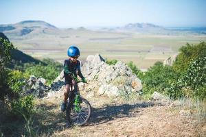 Niño feliz divirtiéndose en el parque de verano con una bicicleta en el hermoso día de otoño foto