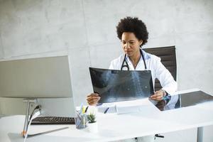 doctor mirando rayos x en el escritorio foto