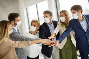 Masked team putting hands together photo
