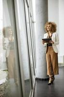 Woman looking out window and holding tablet photo