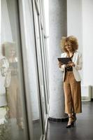 Woman standing near window and holding tablet photo