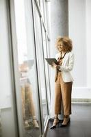 Vertical view of a woman standing near window and holding tablet photo