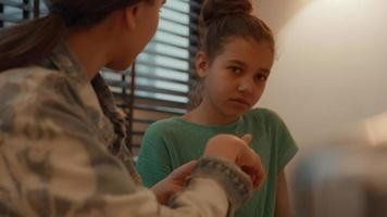 mujer ayudando a niña haciendo los deberes en la mesa video