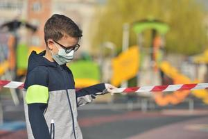 Disappointed lonely kid wearing mask for protection of coronavirus spread photo