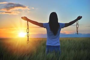 Mujer sintiéndose libre en un hermoso entorno natural en el campo de trigo al atardecer foto