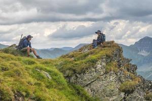 padre e hijo en la cima de la montaña senderismo con mochilas en un día soleado foto