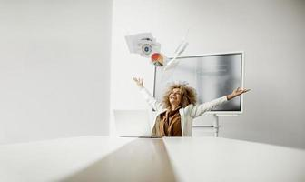 Woman throwing documents in air photo