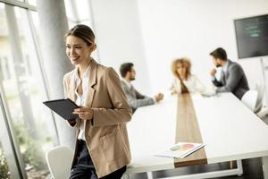 Woman holding a tablet with a meeting in the background photo