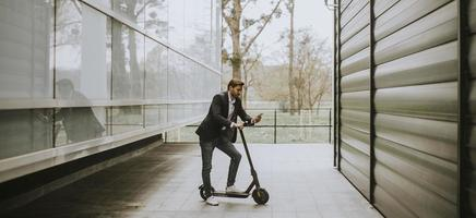 Man standing on scooter while on phone photo
