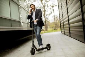 Businessman on phone while standing on a scooter photo