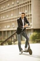 Businessman holding phone while standing on a scooter photo