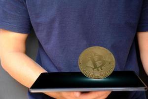 Moneda de criptomoneda en tableta y concepto de dinero en moneda digital foto