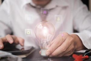empresario sosteniendo bombilla y concepto de innovación tecnológica foto