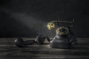 Vintage teléfono negro sobre fondo de mesa de madera vieja foto