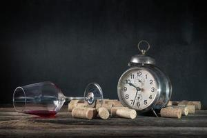 Empty wine glass of alcoholic drink corks and vintage alarm clock concept of alcoholism photo