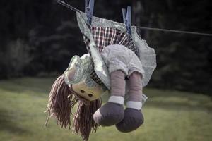Concepto de violencia contra los niños, muñeca pelirroja abandonada en vestido colgando de una cuerda foto