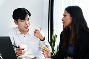 dos jóvenes ejecutivos de empresas discuten cómo cambiar su concepto empresarial para aumentar las ganancias y la solidez de su negocio. foto