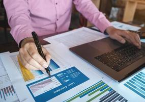 Contador conceptos de contabilidad, mano masculina sosteniendo la pluma apuntando a la solicitud de préstamo con computadora portátil para trabajar, concepto de contador inspector. foto