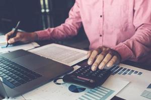 Conceptos de contabilidad contable, calculadora de uso masculino, bolígrafo y computadora portátil para trabajar financiero y presupuestario, concepto de contador inspector. foto