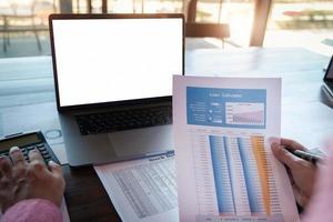 Conceptos de contabilidad de tenedor de libros, mano masculina que sostiene la solicitud de préstamo con calculadora y computadora portátil para trabajar, concepto de contador inspector. foto